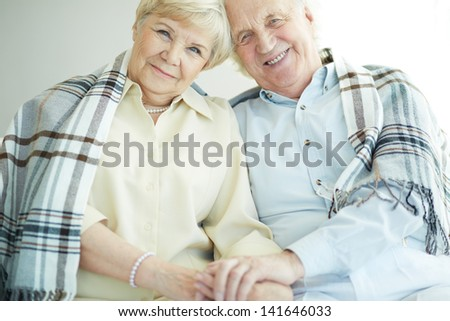 Portrait of cheerful senior couple looking at camera with smiles - stock photo