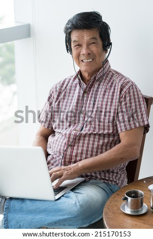 Portrait of cheerful senior man in headset working on laptop - stock photo