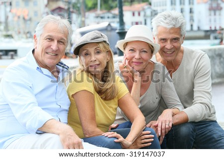 Portrait of cheerful senior people enjoying trip - stock photo