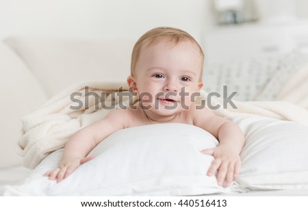 Portrait of cheerful smiling baby boy lying on big bed - stock photo