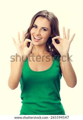 Portrait of cheerful smiling beautiful young woman showing okay gesture in casual smart green clothing - stock photo