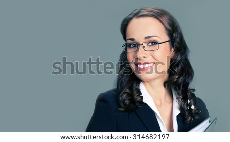 Portrait of cheerful smiling businesswoman in glasses, with folder, with blank copyspace area for slogan or text - stock photo