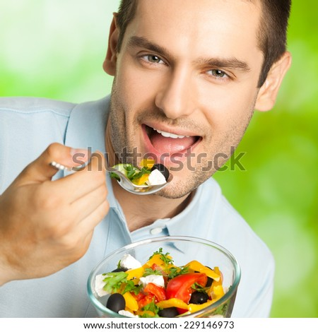 Portrait of cheerful smiling man with salad, outdoor - stock photo