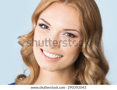 Portrait of cheerful smiling young beautiful blond woman, against blue background - stock photo