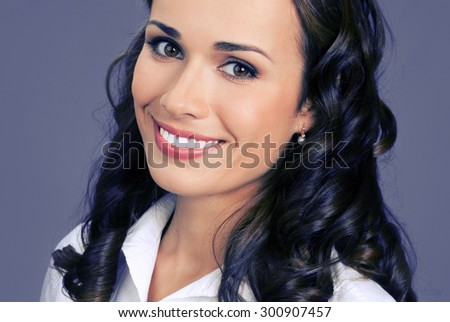 Portrait of cheerful smiling young businesswoman, posing at studio, over violet background - stock photo