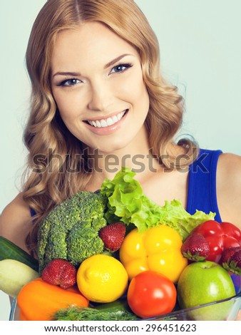 Portrait of cheerful smiling young lovely woman with healthy vegetarian raw food, against blue background. Healthy eating and dieting concept. - stock photo