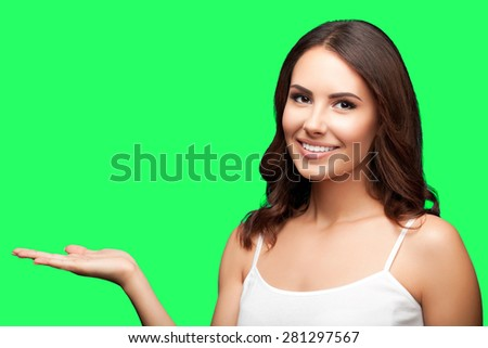 Portrait of cheerful smiling young woman in white casual clothing showing copyspace or something, isolated over green screen chroma key background - stock photo