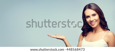 Portrait of cheerful smiling young woman in white casual clothing showing copyspace or something - stock photo