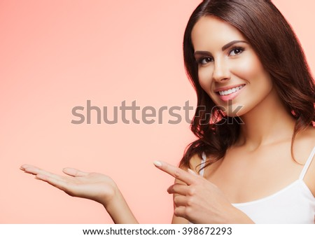 Portrait of cheerful smiling young woman showing copyspace or something, over blue background - stock photo