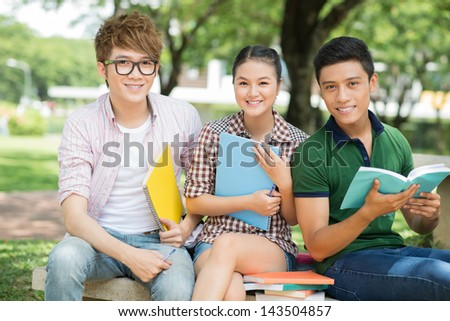 Portrait of cheerful students sitting with notebooks and looking at camera - stock photo