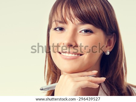 Portrait of cheerful thinking or planning young businesswoman in white business style clothing or student with pen - stock photo
