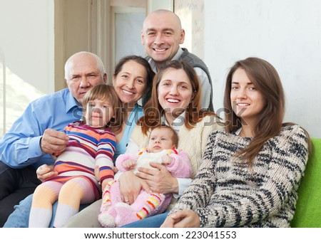 Portrait of  cheerful three generations family sits on sofa in home interior - stock photo