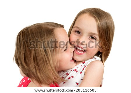 Portrait of cheerful twin sisters hugging , laughing, embracing and smiling at the camera in a studio shoot. Isolated on white - stock photo