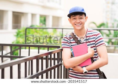 Portrait of cheerful Vietnamese student holding books - stock photo
