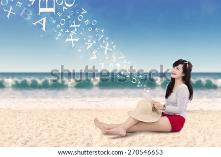 Portrait of cheerful woman sitting on the sand at the beach while using tablet and smiling happy - stock photo