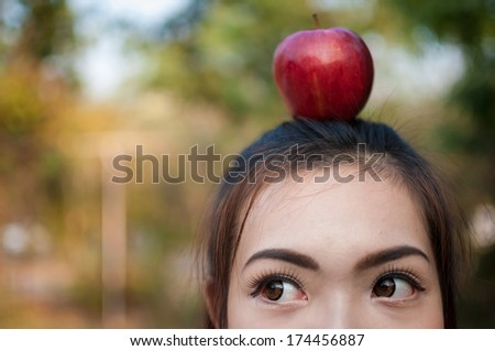 Portrait of cheerful woman with apple on her head - stock photo