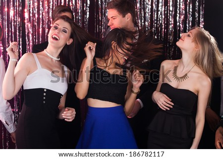 Portrait of cheerful women enjoying party with male friends at nightclub - stock photo