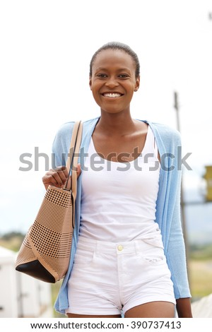 Portrait of cheerful young african woman walking with bag - stock photo