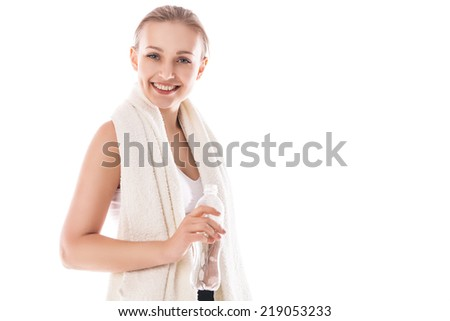 Portrait of cheerful young attractive blond woman in fitness wear with bottle of water and towel, over white background - stock photo