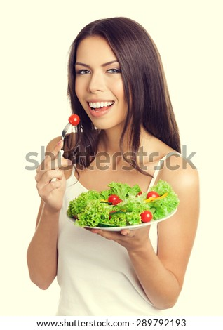 Portrait of cheerful young brunette woman eating vegetarian salad with cherry tomatoes, in tank top casual smart clothing. Healthy eating and dieting concept. - stock photo