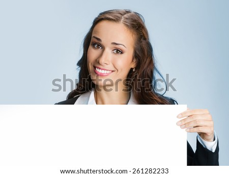 Portrait of cheerful young businesswoman showing blank signboard, against blue background - stock photo