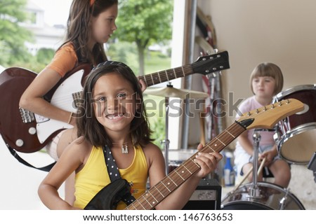 Portrait of cheerful young girl playing guitar with band in garage - stock photo