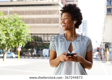 Portrait of cheerful young lady out on the city street listening to music on her mobile phone  - stock photo