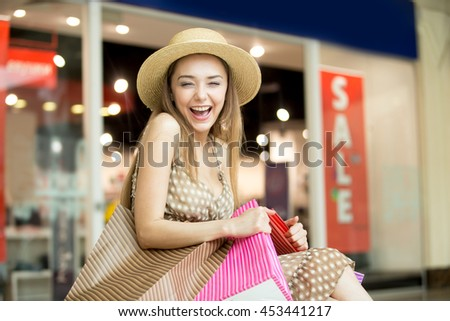 Portrait of cheerful young pretty woman wearing hat in shopping centre, hugging tightly bags with purchases, laughing happily squinted. Fashion, sale, shopping concept. Red sale sign on background - stock photo