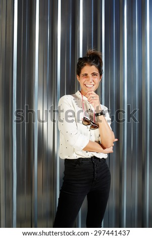 Portrait of cheerful young woman dressed in a glamorous modern clothes standing on shiny chrome background with copy space for your text message, happy teenager smiling brightly to camera in sunny day - stock photo