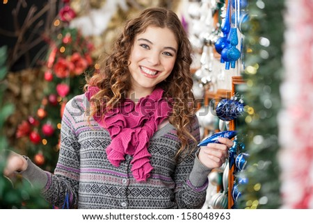 Portrait of cheerful young woman shopping for Christmas ornaments in store - stock photo