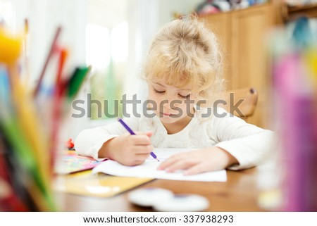 Portrait of child girl drawing at home - stock photo