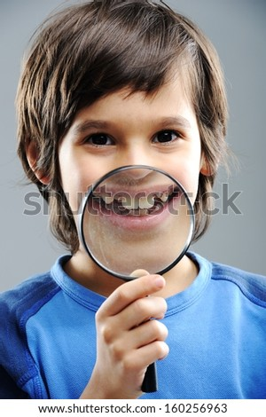 Portrait of child looking closely with magnifying glass - stock photo