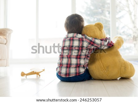 Portrait of child sitting in living room with Teddy bear - stock photo