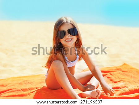 Portrait of child sitting on the beach in sunny day, summer holidays, vacation concept - stock photo
