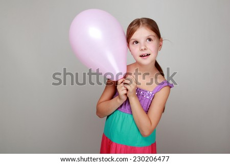 Portrait of child with cute smile in a bright sundress holding colorful balloons on a gray background - stock photo