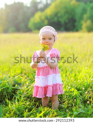 Portrait of child with flowers on the grass in summer day - stock photo