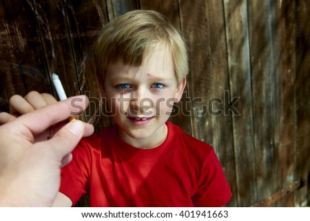 Portrait of Child young schooler boy smoking the Cigarette on the backyard. Teenager secretly smoke the Cigarette, wooden wall background, portrait - stock photo