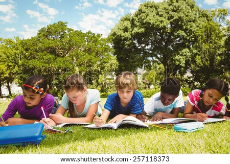Portrait of children doing homework at the park - stock photo