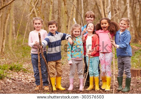 Portrait Of Children Playing Adventure Game In Forest - stock photo