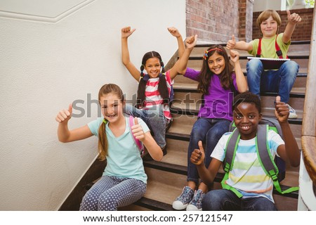 Portrait of children sitting on stairs in the school - stock photo