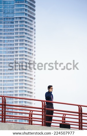 Portrait of chinese businessman standing on bridge in Panama city with skyline in background, answering phone call - stock photo