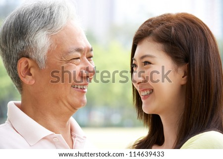 Portrait Of Chinese Father With Adult Daughter In Park - stock photo