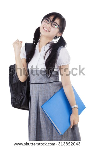Portrait of chinese high school student celebrating success in the studio while carrying backpack, isolated on white - stock photo