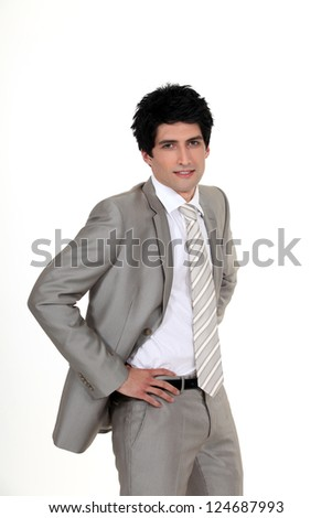 portrait of classy businessman with hands resting on waist - stock photo