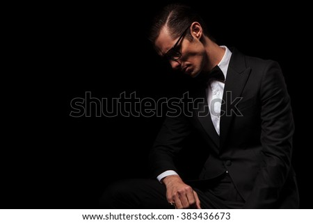 portrait of classy man in black tux wearing glasses posing in dark studio background looking down  - stock photo