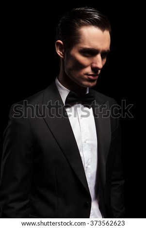 portrait of classy man in tuxedo with bowtie looking away in dark studio background - stock photo