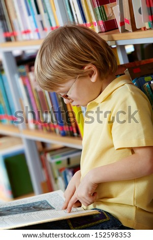 Portrait of clever boy reading book in library - stock photo