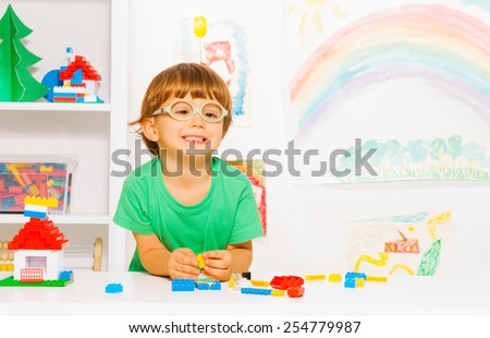 Portrait of clever looking little preschool boy in glasses playing with plastic blocks constructing simple house in the room background - stock photo