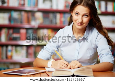 Portrait of clever student looking at camera while working in college library - stock photo