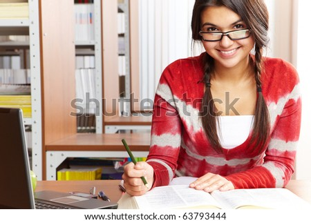 Portrait of clever student preparing lessons in college library - stock photo